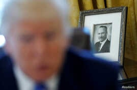 FILE - A photo of U.S. President Donald Trump's late father Fred Trump is seen behind him as he gives an interview in the Oval Office at the White House in Washington, Feb. 23, 2017.