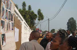 People look at pictures of injured victims in front of the Loandjili hospital in Pointe-Noire, 22 Jun 2010
