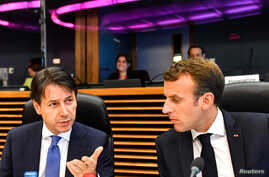 French President Emmanuel Macron, right, speaks with Italian Prime Minister Giuseppe Conte during a round table meeting at an informal EU summit on migration at EU headquarters in Brussels, June 24, 2018.