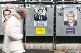 A man walks past electoral posters displaying the presidential candidates, Benoit Hamon, left, Emmanuel Macron, center, and Marine Le Pen in Paris, France, Monday, April 17, 2017.