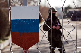 The former emblem of the Ukrainian army is covered in fresh paint in the colors of Russia's flag as a masked member of the newly formed army of Crimea stands behind a gate to a military base in Simferopol, Ukraine, March 13, 2014.