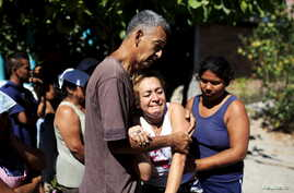 Relatives react as police investigators work at a crime scene where five men were killed in the town of Olocuilta, El Salvador, on Jan. 1, 2016.