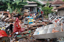 Children affected by the tsunami at Sunda Strait collect snacks from a collapsed shop at Rajabasa in South Lampung, Indonesia, Dec. 25, 2018.