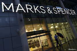 A man leaves a Marks & Spencer store in London, Britain.