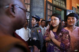 Student Chaw Sandi Tun, 25, speaks with a Buddhist monk after her hearing at court in Maubin, Myanmar, Tuesday, Nov. 24, 2015.
