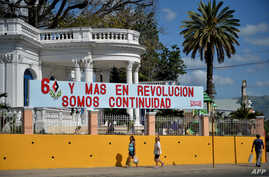 People walk past a banner of the 60th anniversary of the Cuban revolution in Santiago de Cuba, Cuba, Dec. 31, 2018.