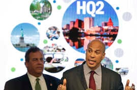 FILE - New Jersey Sen. Cory Booker (R) speaks as New Jersey Gov. Chris Christie stands behind him in Newark, N.J., Oct. 16, 2017, as he announces that New Jersey lawmakers are submitting a bid to Amazon that Newark would be the best location for the
