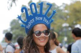 Chilean tourist Paula Aedo ushers in 2017 as she arrives to watch New Year's fireworks in Sydney, Australia, Dec. 31, 2016.