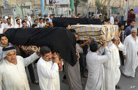 FILE - Mourners carry the coffins of victims of a suicide bombing, in the Shula neighborhood of Baghdad, Iraq, Oct. 12, 2014.