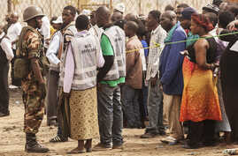 FILE - A Malawian soldier stands guard while Malawians wait in line to cast their ballots, May 21, 2014.