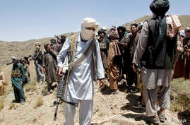 FILE - Members of a Taliban breakaway faction walk during a gathering, in Shindand district of Herat province, Afghanistan, May 27, 2016.