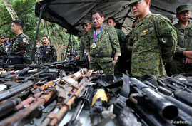 Philippine President Rodrigo Duterte inspects firearms together with Eduardo Ano, Chief of Staff of the Armed Forces of the Philippines (AFP), during his visit at the military camp in Marawi city, southern Philippines, July 20, 2017.