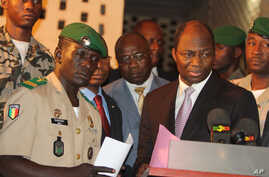 Coup leader Capt. Amadou Haya Sanogo, left, stands with Burkina Faso Foreign Minister Djibrill Bassole, right, as they address the media at junta headquarters in Kati, outside Bamako, Mali, April 6, 2012.