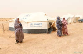 FILE - Libyan women displaced from the town of Tawergha are seen at a camp in the Garart al-Gatef, Libya, March 25, 2018.