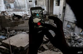 FILE - A Syrian gamer uses the Pokemon Go application on his mobile to catch a Pokemon amidst the rubble in the besieged rebel-controlled town of Douma, a flashpoint east of the capital Damascus, July 23, 2016.