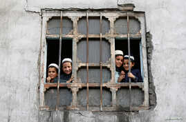 Afghan students from a religious school look on from a window of their school in Kabul, Afghanistan Oct. 5, 2016.