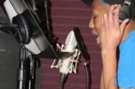 Music clubhouse member, Yung Fresh, in the studio recording his own songs.