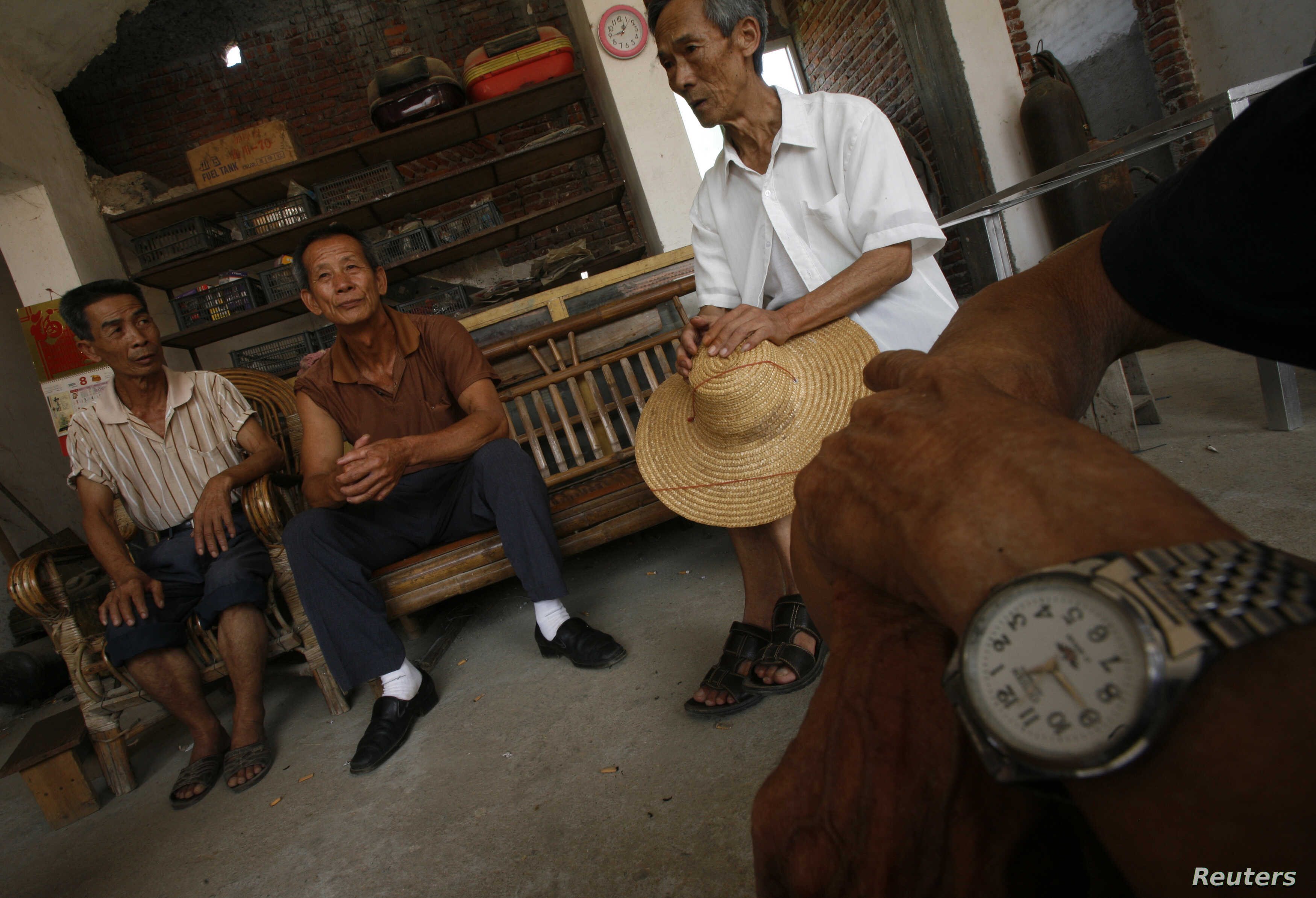 He Kangcai (L), 60, who is suffering from stomach cancer, chats with fellow villagers in his home at Shangba village in the northern part of China's Guangdong province August 27, 2009.