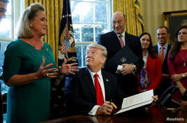 U.S. President Donald Trump looks up at Rep. Ann Wagner after signing an executive order on financial system regulation at the White House in Washington, Feb. 3, 2017.