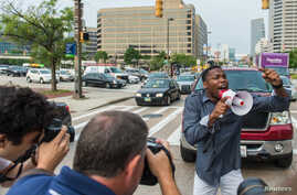 A demonstrator blocks traffic as protests moved into the street on the first day of pretrial motions for six police officers charged in connection with the death of Freddie Gray in Baltimore, Maryland, Sept. 2, 2015.