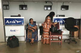 Stranded passengers stand at the closed Arik Air check-in counter following a protest over unpaid salaries by staff in Lagos, Nigeria, Tuesday, Dec. 20, 2016.