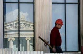 FILE - A worker carries construction material atop the 19th century Athens Academy building in central Athens, Greece.