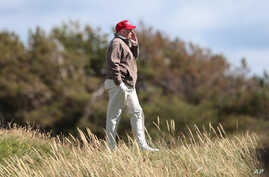 FILE - U.S. Presidential contender Donald Trump walks near the 16th green of the Turnberry golf course in Turnberry, Scotland, July 30, 2015. A British online petition seeks to ban Trump from entering the UK following his comments on Muslims.
