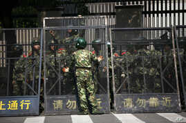 Paramilitary police officers arrange the steel fence at the Japanese Consulate General in Shanghai, China after angry protests over Japan's wartime occupation and Tokyo's recent purchase of islands also claimed by Beijing, Sept. 19, 2012.