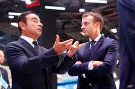 French President Emmanuel Macron listens to Carlos Ghosn, the CEO of French car maker Renault, left, at the Renault stand during an official visit at the Paris Motor Show, in Paris, France, Oct. 3, 2018.