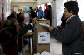 A woman casts her vote at a polling station in Buenos Aires, Argentina, Oct. 25, 2015.