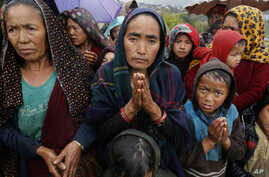 A female villager named Ramaya clasps her hands as she pleads for food after an aid relief helicopter lands at the remote mountain village of Gumda, near the epicenter of Saturday's massive earthquake in the Gorkha District of Nepal, April 29, 2015.