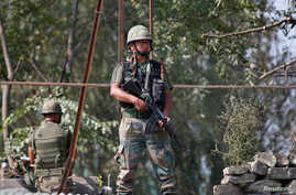 Indian army soldiers keep guard on top of a shop along a highway on the outskirts of Srinagar, Sept. 29, 2016.