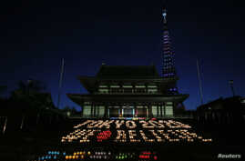 """A message reading """"Tokyo 2020 We Believe"""", made up of 2,020 candles, is displayed at Zojoji temple in Tokyo September 5, 2013."""