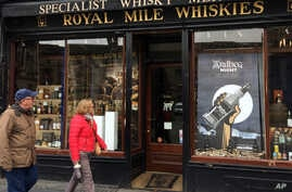 """In this picture taken on Saturday, May 28, 2016, a man and a woman pass a whisky shop on the """"Royal mile"""" in Edinburgh, Scotland. Scotch Whisky Distillers, small and large, are very supportive of the UK's membership of the European Union. Scotch Whis"""