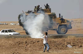 A protester throws stones at an armored army vehicle during a pro-Kurdish demonstration in solidarity with people of Kobani, near the Mursitpinar border crossing on the Turkish-Syrian border, in the Turkish town of Suruc in southeastern Sanliurfa pro