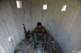 A Turkish-backed Free Syrian Army fighter rests at mount Bafliyun, in the Afrin region, Syria.