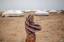 In this May 19, 2015 photo, Ashwaq stands outside her family's tent, at the Markaze refugee camp in Obock, northern Djibouti. Fleeing the war at home, thousands of Yemenis have made it across the Gulf of Aden to find refuge in Djibouti.