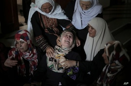 Palestinian relatives of the five members of the Hamad family who were killed in an Israeli missile strike late Tuesday grieve in the family house during their funeral in town of Beit Hanoun, northern Gaza Strip, July 9, 2014.