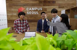 Employees of Dable, a startup and ventures investor, stand around a table during a media tour at the Google campus in Seoul, South Korea, Friday, May 8, 2015.