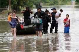FILE - Residents walk through floodwaters after being evacuated from their flooded apartment complex, in Houston.