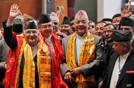 Nepal's newly-appointed prime minister Khadga Prasad Oli, left, waves to the media as he stands with other leaders of Communist Party of Nepal (Unified Marxist–Leninist), also known as CPN-UML, inside the Constituent Assembly in Kathmandu, Oct. 11, 2