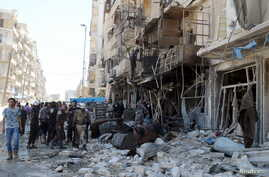 Residents and civil defence members inspect a damaged building after an airstrike on the rebel-held Tariq al-Bab neighbourhood of Aleppo, Syria, April 23, 2016.