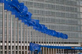 Workers adjust the EU flags in front of EU headquarters in Brussels, Belgium, June 22, 2016. Voters in the United Kingdom are taking part in a referendum that will decide whether Britain remains part of the European Union or leaves the 28-nation bloc...