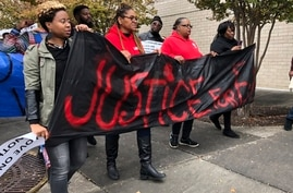 """Protesters carry a sign reading """"Justice for E.J."""" during a protest at the Riverchase Galleria in Hoover, Ala., Nov. 24, 2018. A police officer shot and killed 21-year-old Emantic Fitzgerald Bradford, Jr. of Hueytown while responding to a shooting at"""