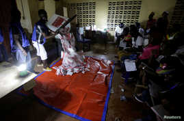 Polling agents start to count the ballots for the Liberian presidential election at a polling station in Monrovia, Liberia, Oct. 10, 2017.