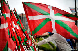 A man returns a Basque flag at the end of a rally in support of ETA prisoners in Bilbao, Spain, April 21, 2018, following an apology released by armed separatists ETA , and amid news of the group's dissolution.