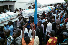 Mourners carry coffins containing the bodies of protesters killed in September demonstrations organised by the Union for Democracy and Social Progress (UDPS), during a funeral service at the UDPS headquarters in Limete, Kinshasa, Democratic Republic