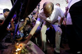 Former Philippine President Benigno Aquino III places a candle under a picture of victims of alleged extrajudicial killings after a mass at the University of the Philippines Church of the Holy Sacrifice to commemorate the 45th anniversary of the impo...
