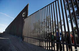 Boys look through an older section of the border structure from Mexicali, Mexico, alongside a newly constructed, taller section, left, in Calexico, Calif., March 5, 2018. President Trump tweeted about new work on the border wall, but this work isn't ...
