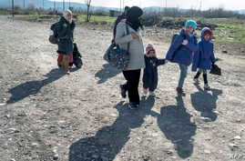 A woman and children cross the Greek-Macedonian border near the town of Gevgelija on February 25, 2016. European interior ministers tried on February 25 to resolve deep divisions over the migrant crisis, with Greece lashing out at its partners for cr...